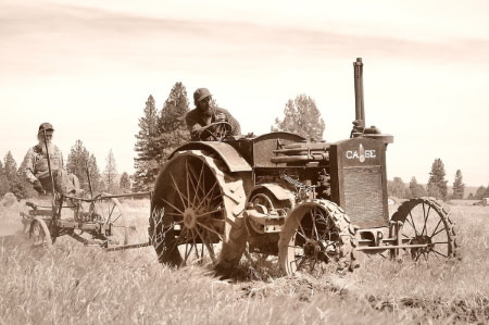father and son using old farm equipment