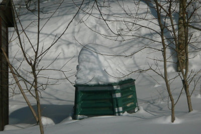 Compost bin in the winter with snow piled on top