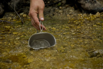 dipping cup into stream water
