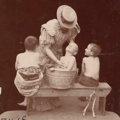 mom washing kids in old vintage tub