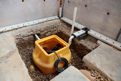 sump hole with sump pump installed in basement