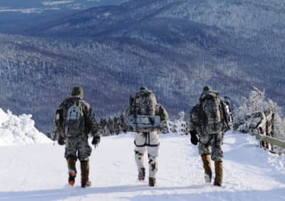 men with tactical gear hiking in the snow and mountains