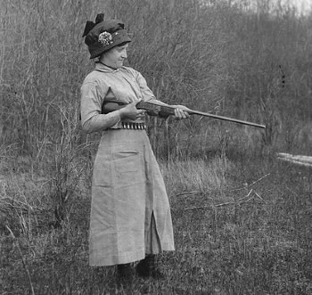 antique photo of woman shooting a shotgun