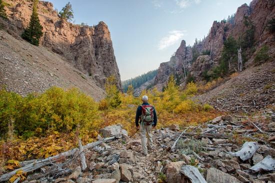 man backpacking through remote mountains